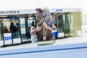 Der Fotograf Urs Kuester mit seiner kleinen Tochter auf dem Arm, fotografiert in die Spiegelung einer Scheibe am Flughafen Hamburg. Es ist ein Selbstportrait.