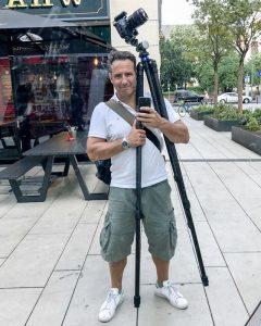 Der Fotograf Urs Kuester mit Kameratasche und Stativ, fotografiert in die Spiegelung einer Scheibe. Es ist ein Selbstportrait.