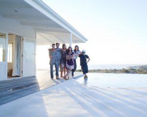 Ein Teamfoto mit dem Fotografen Urs Kuester und seinem Fotoproduktionsteam in einem Strandhaus mit Pool bei Kapstadt. Sechs Personen schauen in die Kamera im Sonnenuntergang. Im Hintergrund ist das Meer zu sehen.