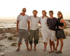 Ein Teamfoto mit dem Fotografen Urs Kuester und seinem Fotoproduktionsteam am Strand von Kapstadt. Fünf Personen schauen in die Kamera im Sonnenuntergang.