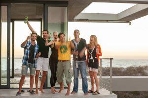 Der Fotograf Urs Kuester mit seinem Fototeam in einer Fotolocation in Kapstadt. Es ist eine moderne Architektur mit Glas und Beton. Es sind sechs Personen zu sehen, die in die Kamera lachen und eine Flasche Champagner öffnen. Im Hintergrund ist ein Strand und das Meer zu sehen. Das Bild entstand anlässlich einer Fotoproduktion für Nivea.