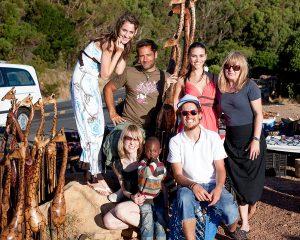 Sieben Personen posieren für die Kamera auf einem Straßenmarkt in Campsbay/ Kapstadt. Es sind geschnitzte Holzgiraffen und allerlei Schmuck zu sehen. Ein kleiner Junge hat sich zu dem Fototeam von Fotograf Urs Kuester gestellt.