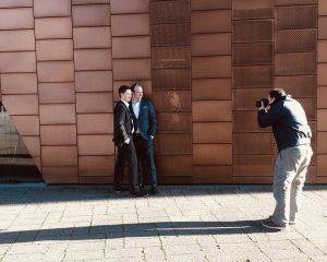 Casini und Görner Geschäftsinhaber Enrico Casini und Patrick Görner stehen im Anzug an einer Kupferfarbenen Wand und werden von dem Hamburger Fotografen Urs Kuester fotografiert.