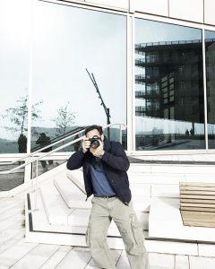 Der Fotograf Urs Kuester in Aktion mit der Kamera im Anschlag auf einer modernen Location in der Hafen City Hamburg.